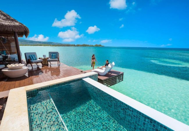 guests relaxing on the balcony of the over the water villas in the caribbean
