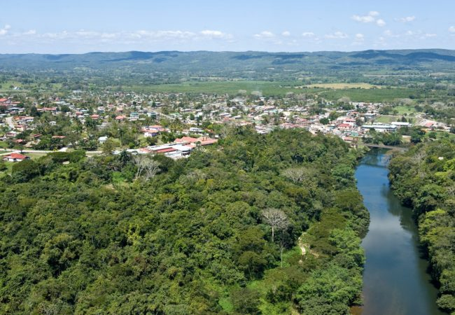an ariel view of the macal river with san ignacio town in the background