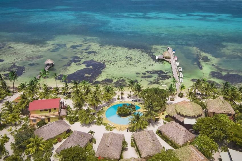 aerial view of the cabanas, pool and dock at portofino beach resort on ambergris caye in belize