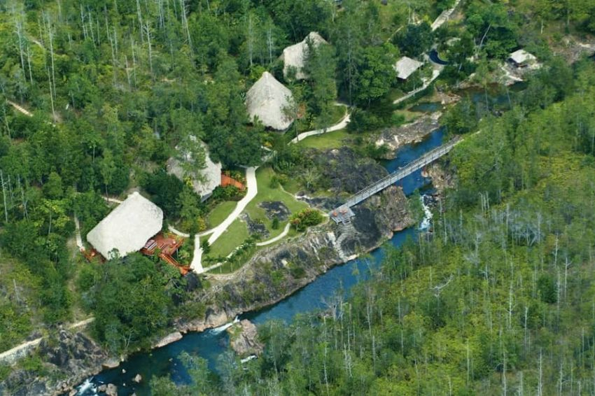 aerial view of blancaneaux lodge in the pine forest next to a creek in belize