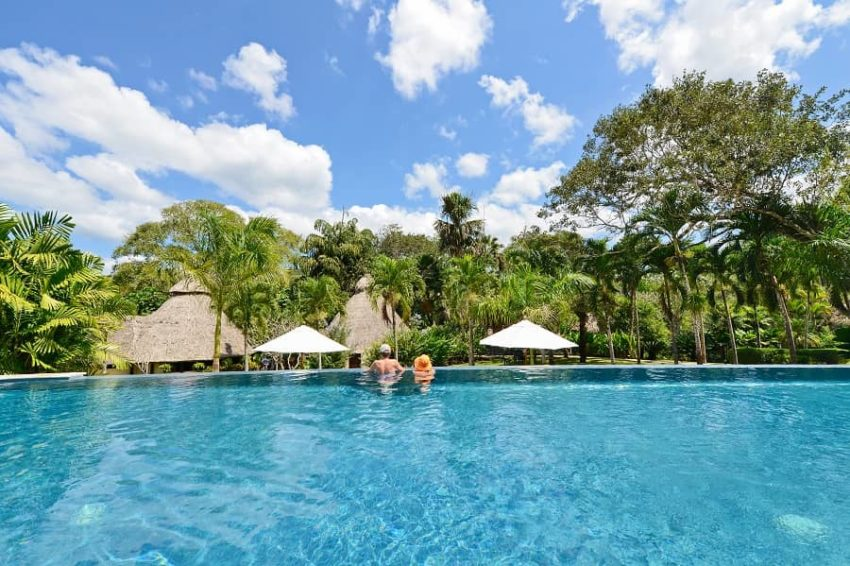 guests relaxing at the end of the eco infinity pool that overlooks the jungle of belize at chaa creek