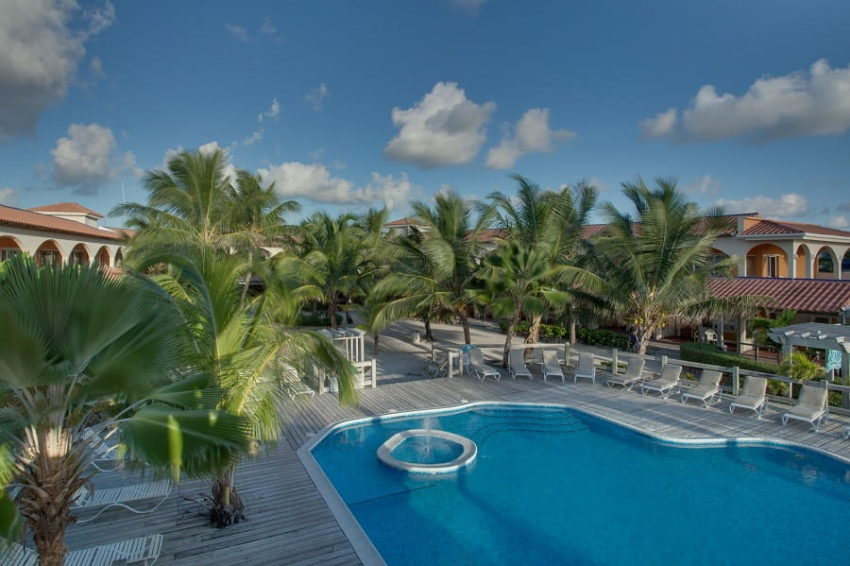 the courtyard with the pool and restaurant at sunbreeze hotel on the island of ambergris caye in belize