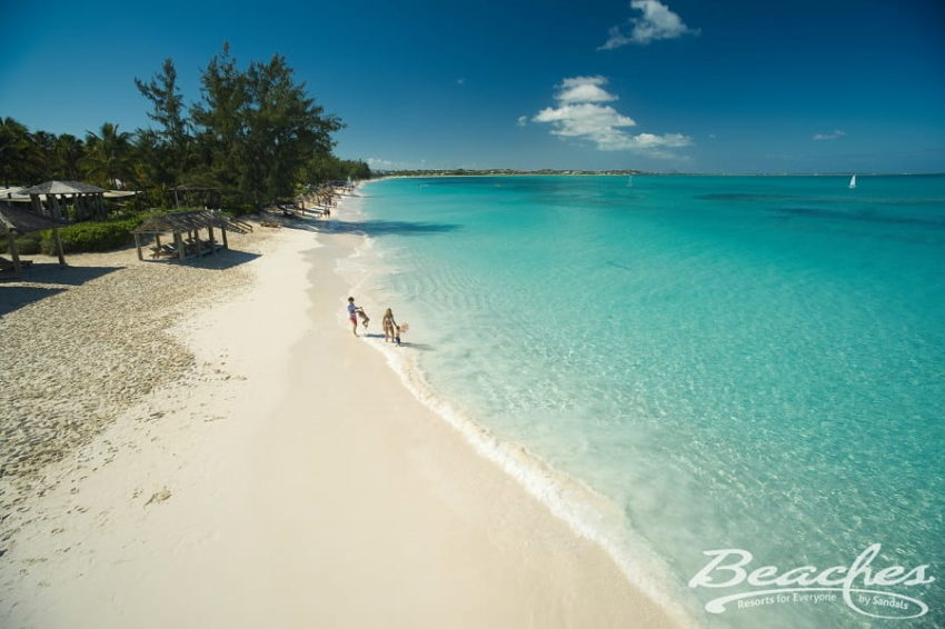 family walking on the beach next to cyrstal clear caribbean waters at beaches turks & caicos
