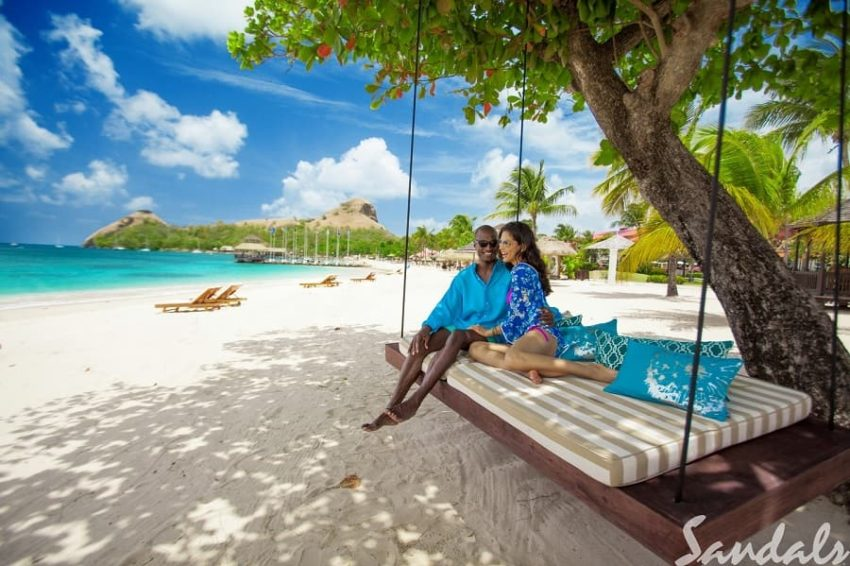 couple relaxing on the beach hammock at sandals grande st lucian in st lucia a sandals all inclusive resorts