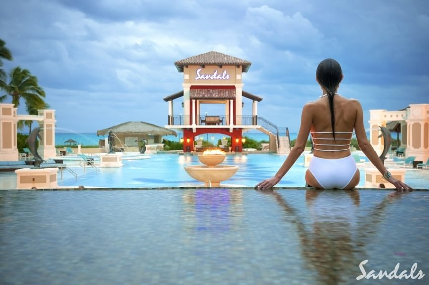 a guest sitting in the pool overlooking the caribbean sea at sandals emerald bay in the bahamas