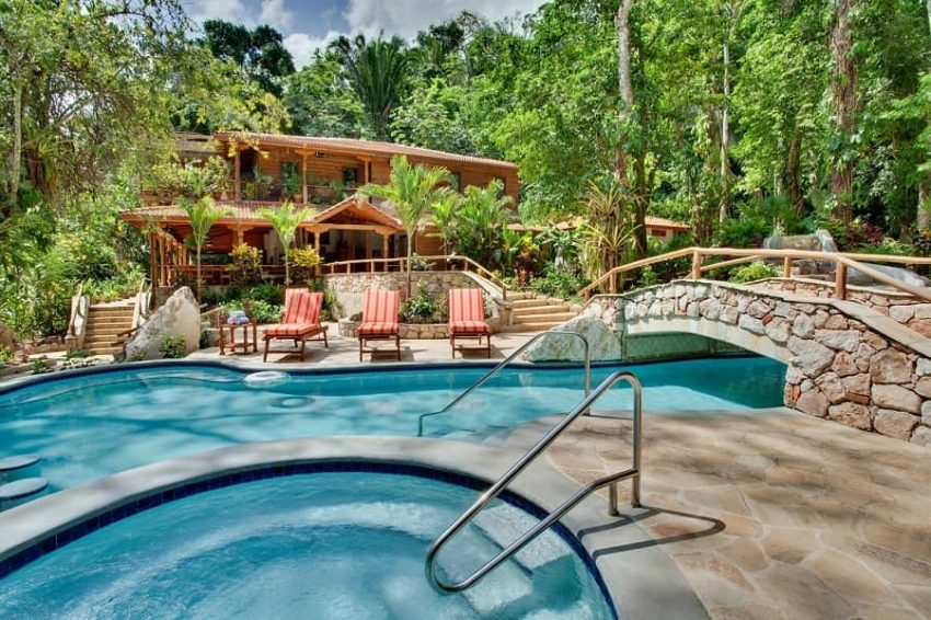the main lodge surrounded by jungle with a view of the pool at cave branch lodge belize