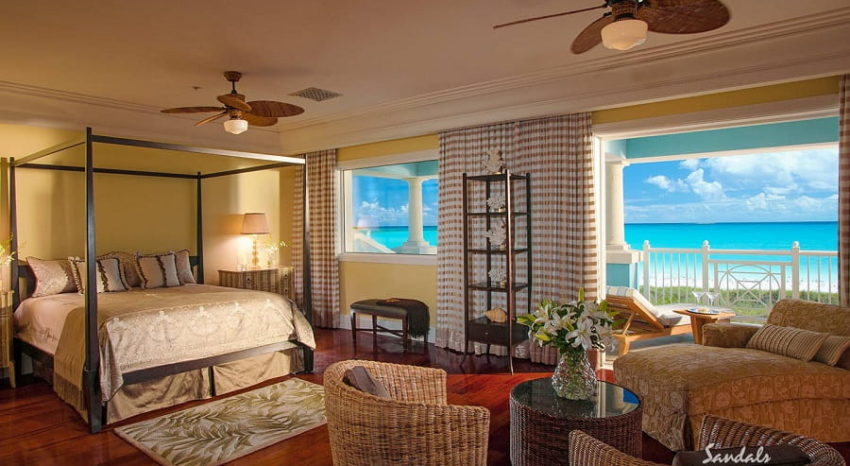 the bed, sitting chair and balcony overlooking the caribbean sea from the royal estate beachfront two story one bedroom bulter villa at sandals emerald bay in the bahamas