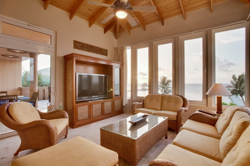 the living room with floor to ceiling windows that overlook the caribbean sea at villa del mar at belizean cove estate