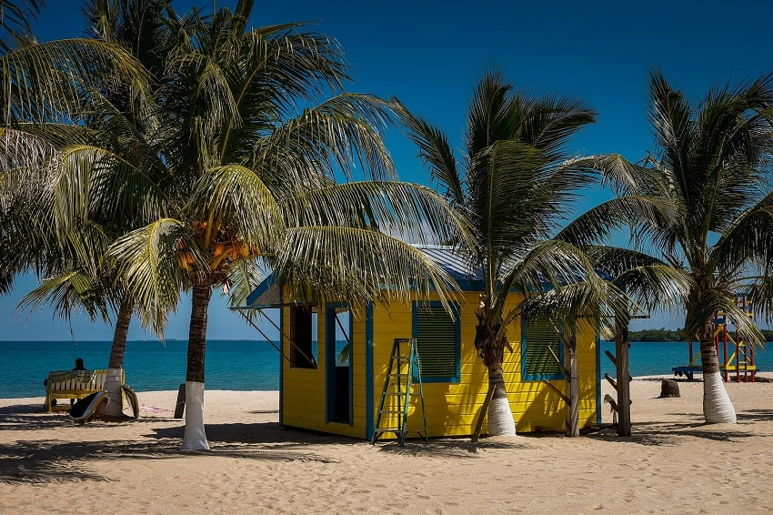 placencia beach with yellow cabin and coconut trees in belize