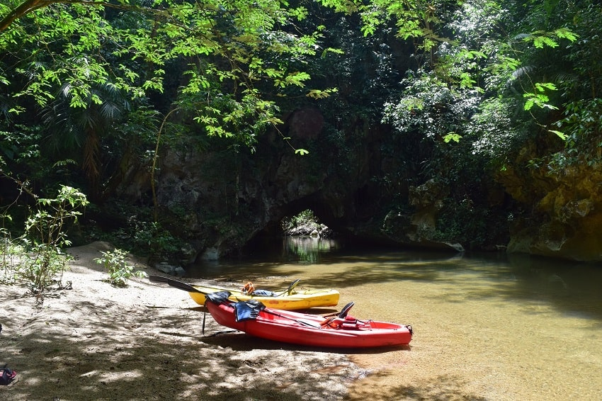 red and yellow kayak on a sandy beach on a river with a jungle and a cave in the background