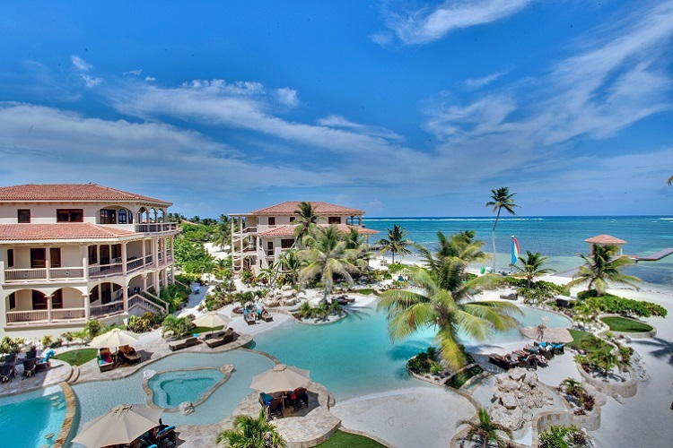 seaview, beachfront with the beachfront pool with coconut trees at coco beach resort on the island of ambergris caye