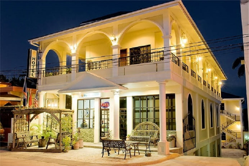 view of the front of hotel de la fuente at night in downtown orange walk belize